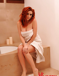 The bath fills up and the redheaded curvy girl hops inside for a dip